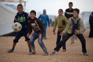 Kids play football in the Za'atari refugee camp in Jordan. Football is a 'mother'.